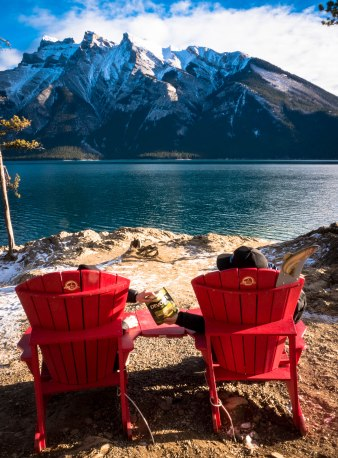devour-cao-ab-landmark-banff-lake-minnewanka-with-red-chairs-sharing-jerky-3-edited
